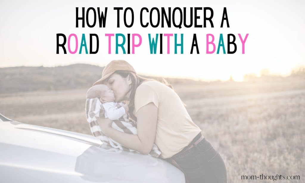 This is an image of a mother holding her baby on the hood of a car giving him a kiss on the cheek. There is text that says How To Conquer A Road Trip With A Baby. The image is on a post that outlines tips for going on a long road trip with a baby.