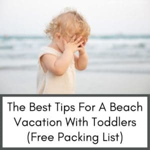 this is an image of a toddler at the beach. The toddler has blonde hair and is on the beach covering her face with her hands. You can see the ocean water in the back.