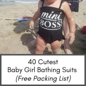 Image shows a baby on the beach in a black baby bathing suit