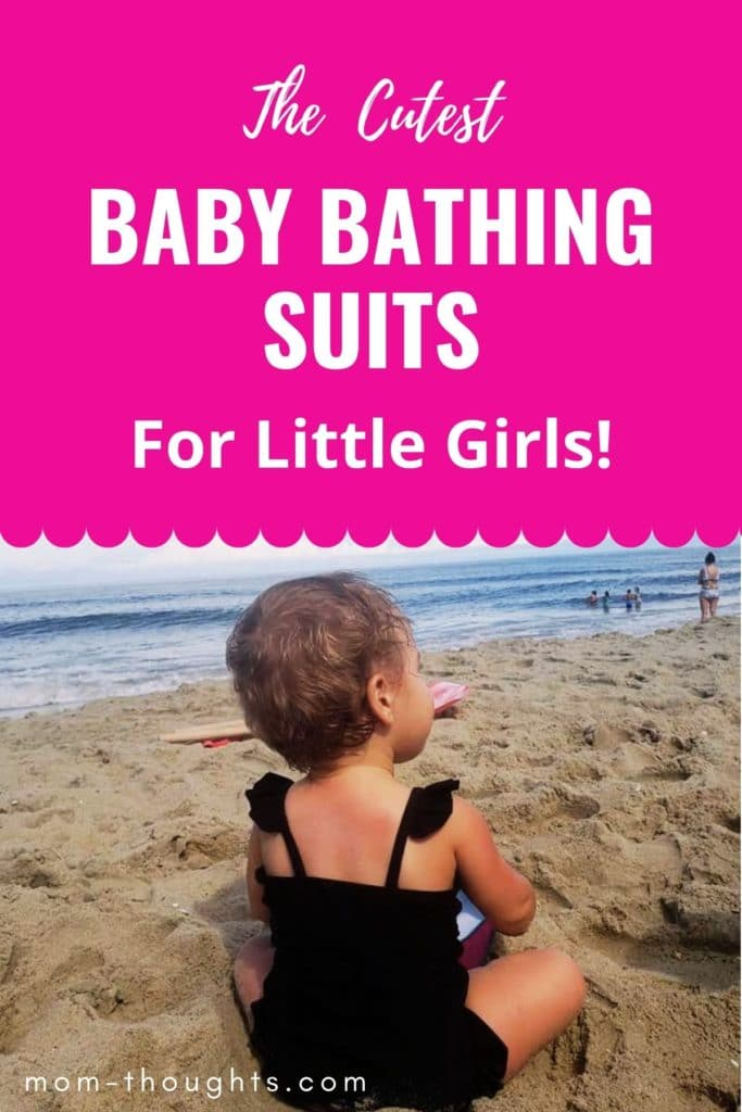"""This image has a baby girl sitting on the beach in a black baby bathing suit. The top of the image is hot pink and has white text that says """"The Cutest Baby Bathing Suits For Little Girls!"""""""