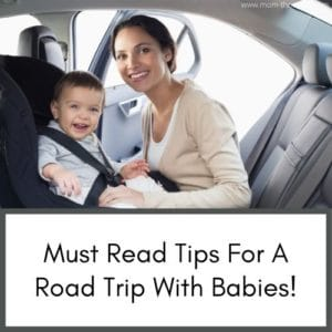 This image is of a baby in a car seat with the mom while on a road trip with baby. Both smiling at the camera.