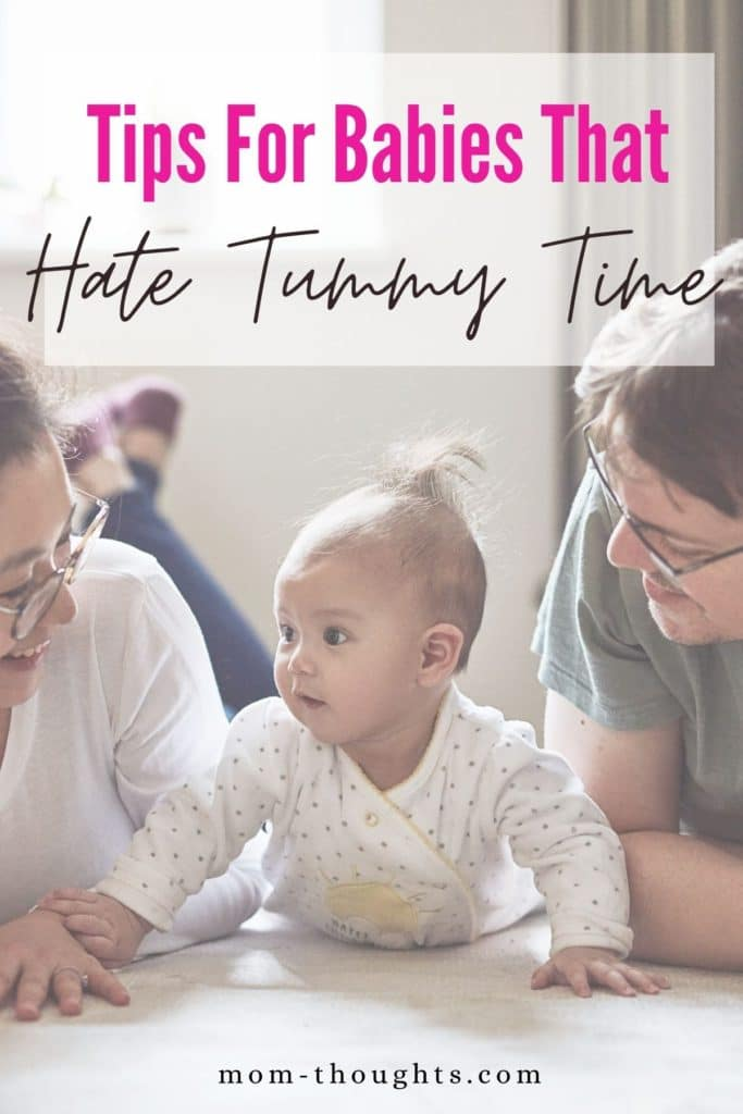 """This image shows a picture of a mom and dad on the floor with their baby doing tummy time. The baby is in between the mom and dad. There is a white faded rectangle with text that says """"Tips for babies that hate tummy time"""""""