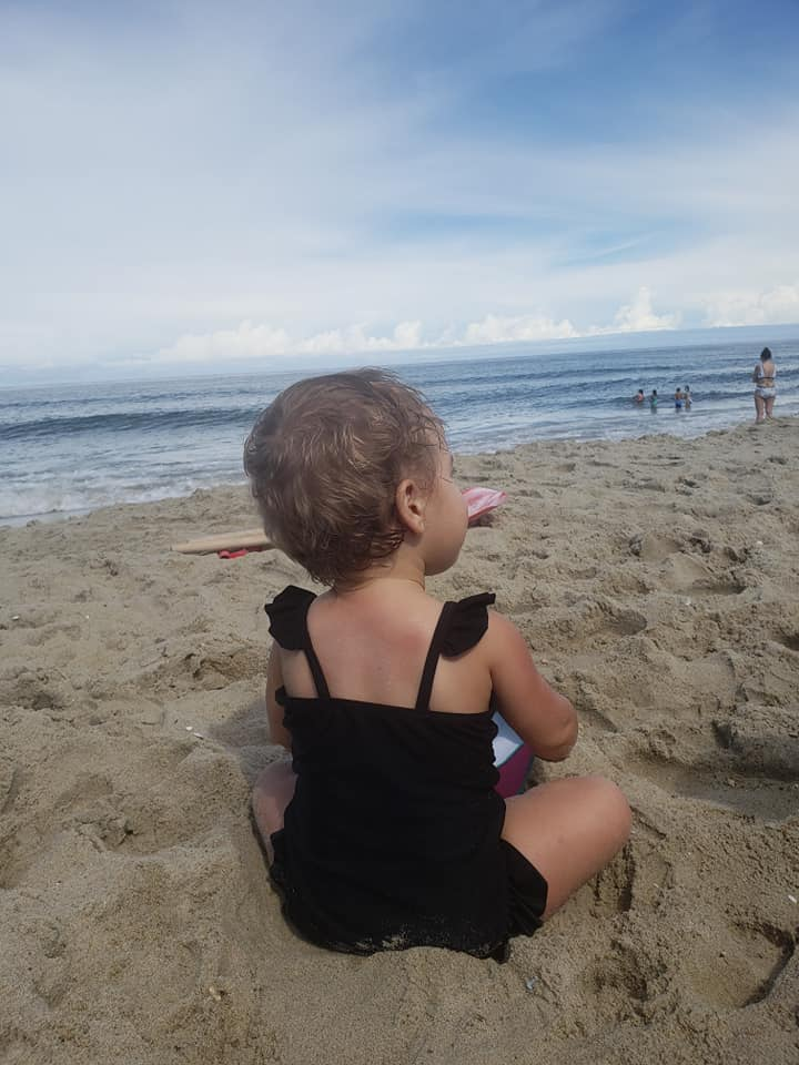 This image shows a baby girl sitting on the beach in a black baby bathing suit