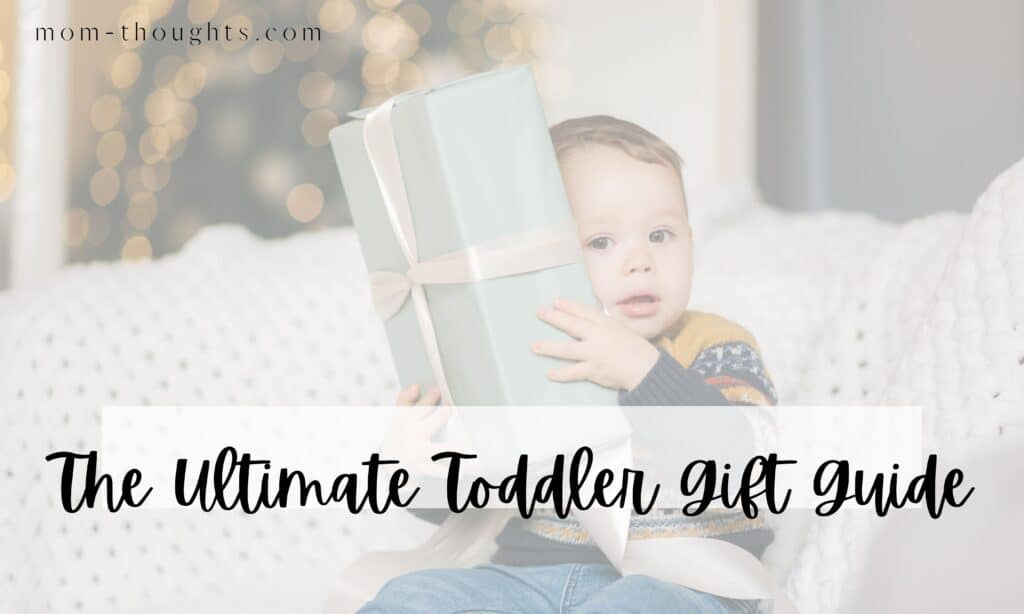"""This image is of a toddler boy sitting on a couch holding a present up to his face. There is text overlay that says """"The Ultimate Toddler Gift Guide"""". The image is on a post that lists out the best gifts for toddlers."""