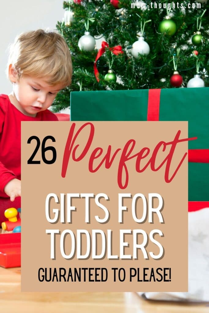 """This image is of a toddler boy sitting in front of a Christmas Tree opening a present. There is text overlay that says """"26 perfect gifts for toddlers guaranteed to please!"""""""