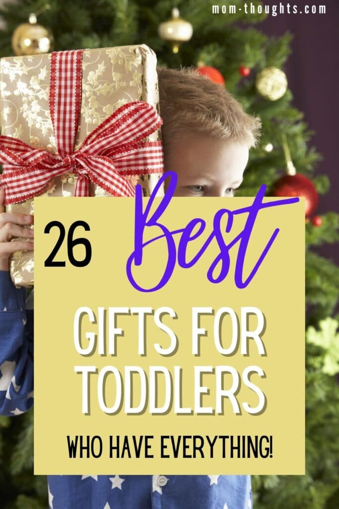 """This image is of a toddler boy holding a present up to his face. The present has a big red ribbon. There is text overlay that says """"26 best gifts for toddlers who have everything!"""""""