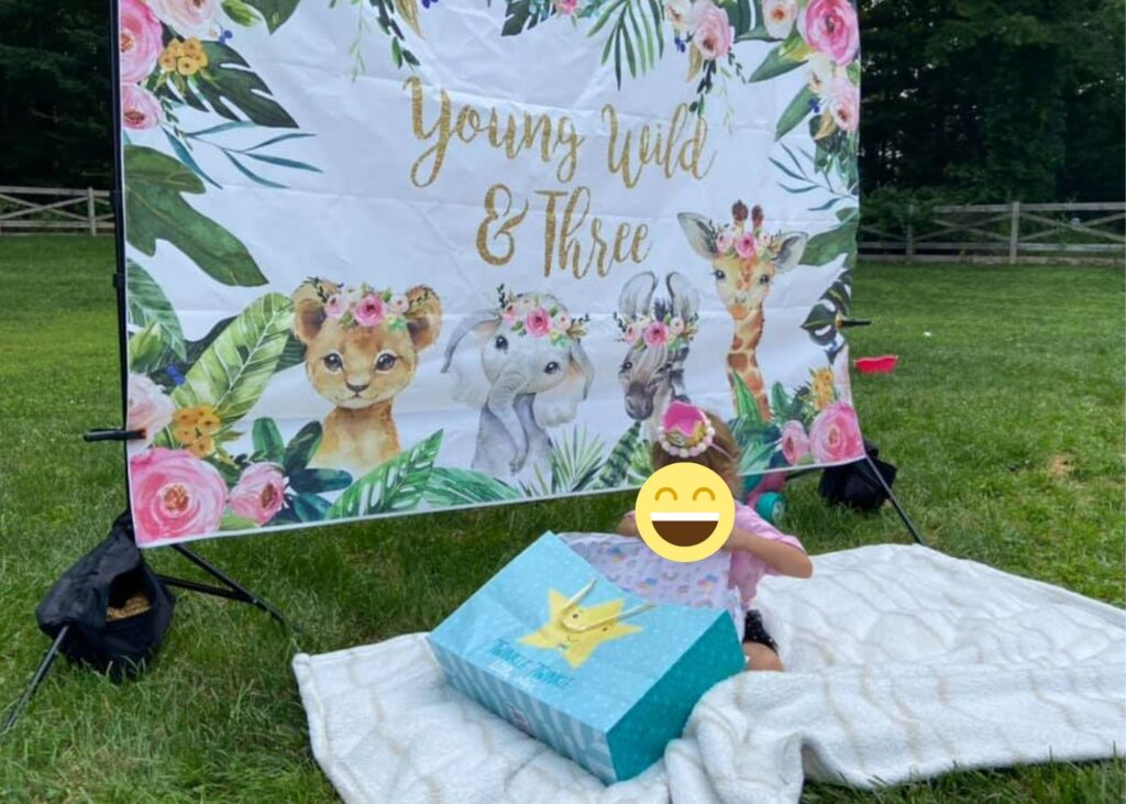 """This image shows a three year old opening presents for their 3rd birthday party. They are in front of a backdrop that says """"young wild and three"""""""