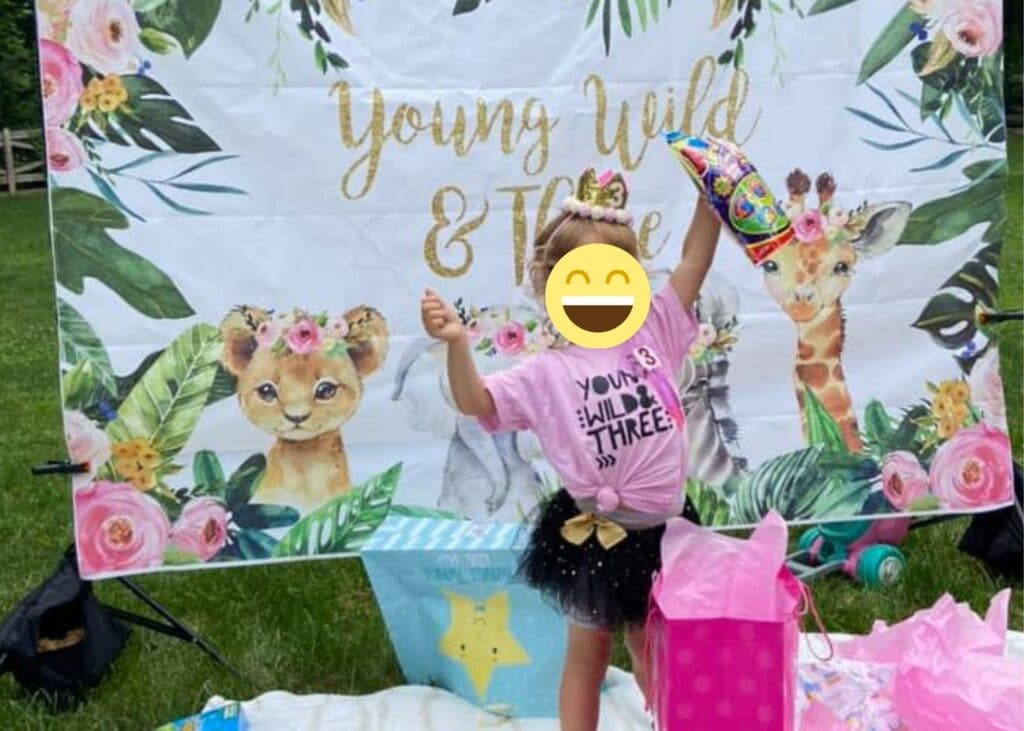 """This image shows a little girl opening gifts, wearing a pink """"Young Wild and Three"""" birthday shirt and black tutu. She's standing in front of a banner/backdrop that says Young Wild and Three. Her face is covered with a smiley face."""