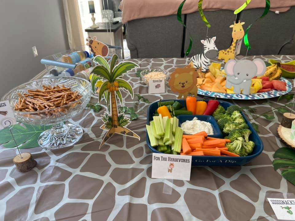 This image shows appetizers at a Young Wild and Three Birthday party. There are printable food labels. There's a giraffe print table cloth covering the table.